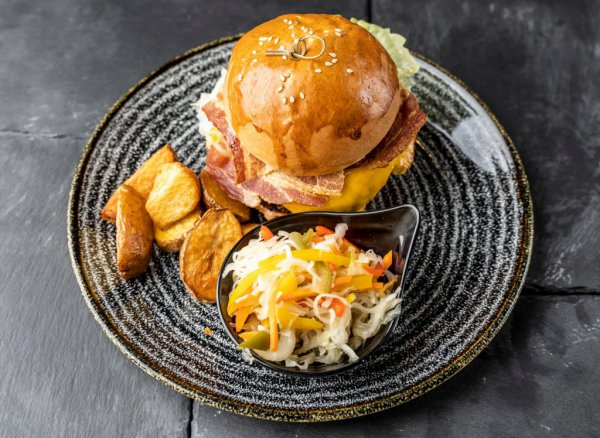 Beef hamburger with potato wedges and cabbage salad